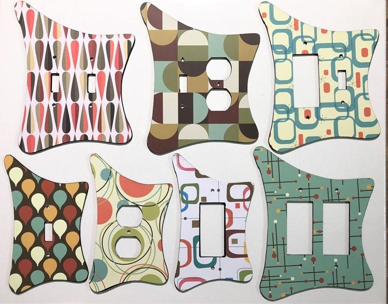 A display of seven retro light switch covers in different patterns