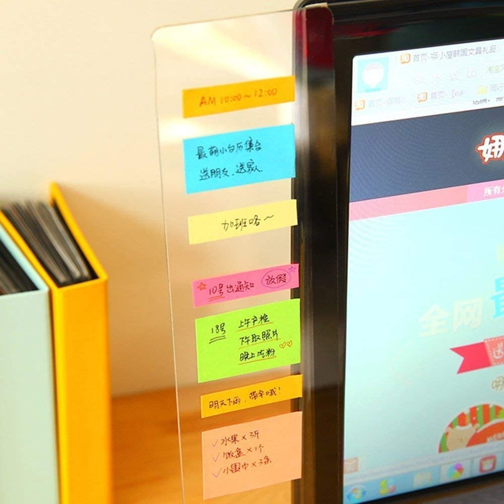 A clear panel is pasted on the edge of a monitor with sticky notes on it