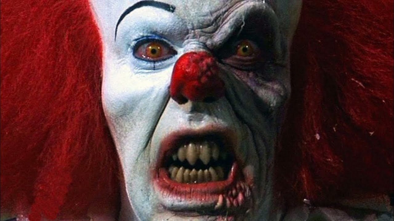 A close up of Pennywise in creepy clown makeup staring menacingly at camera
