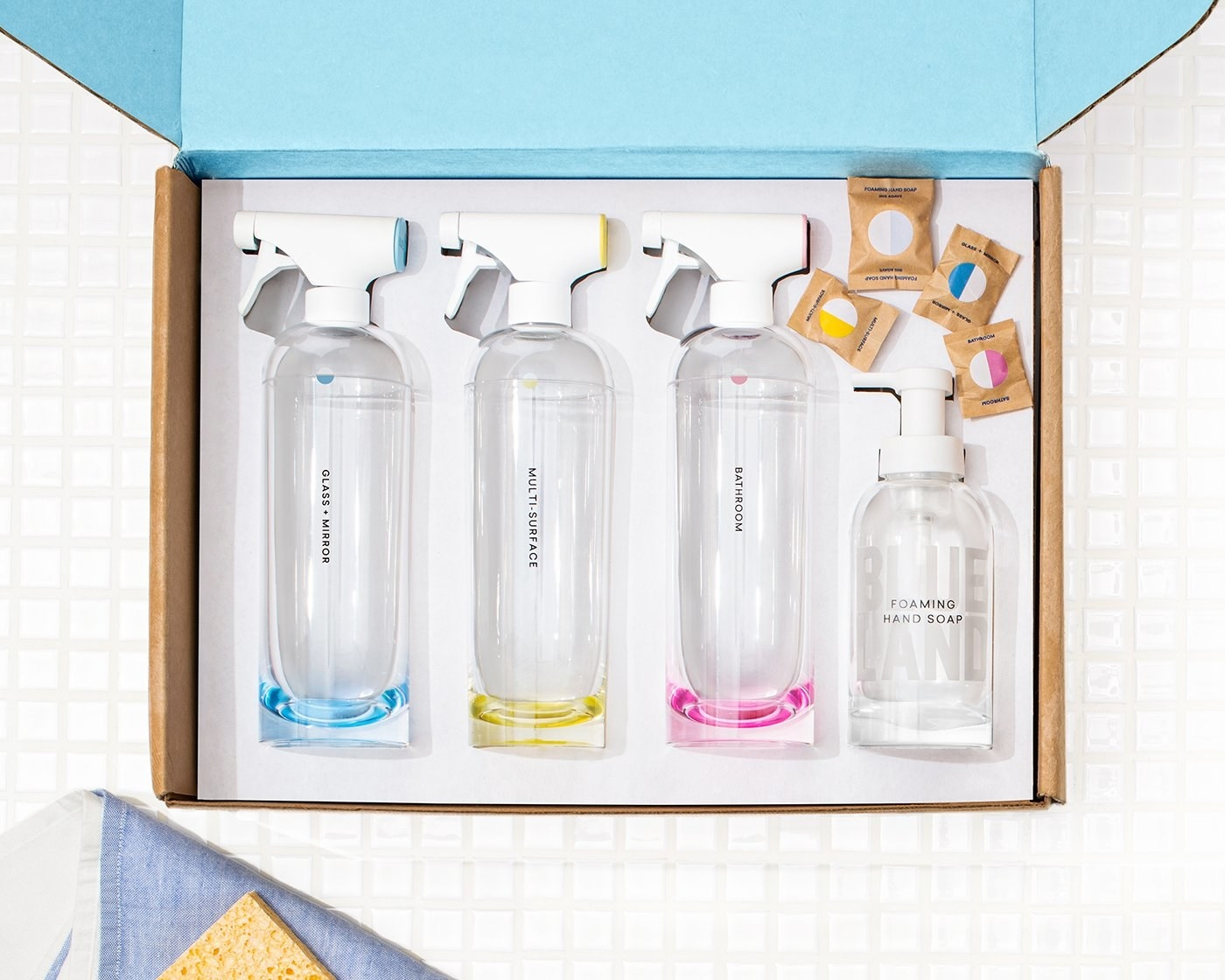 A box with three tall clear bottles and one small clear bottle and four small packets in the top right corner