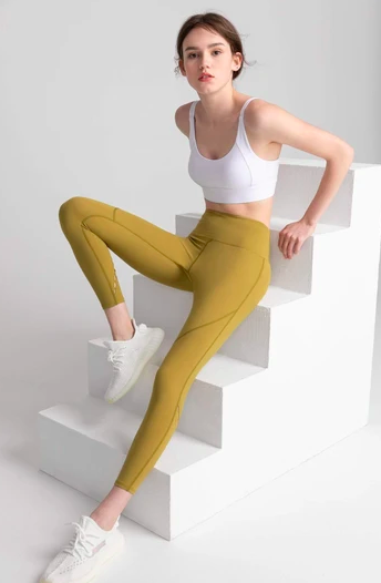 Model wears citrus-colored high-rise leggings with a white crop top and sneakers