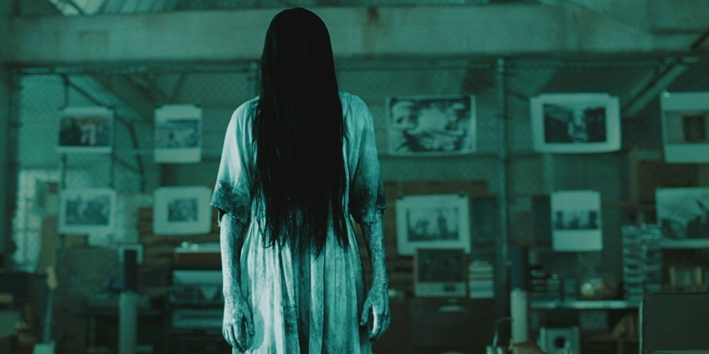 Samara stands in a dirty dress with her hair in front of her face in a dimly lit room