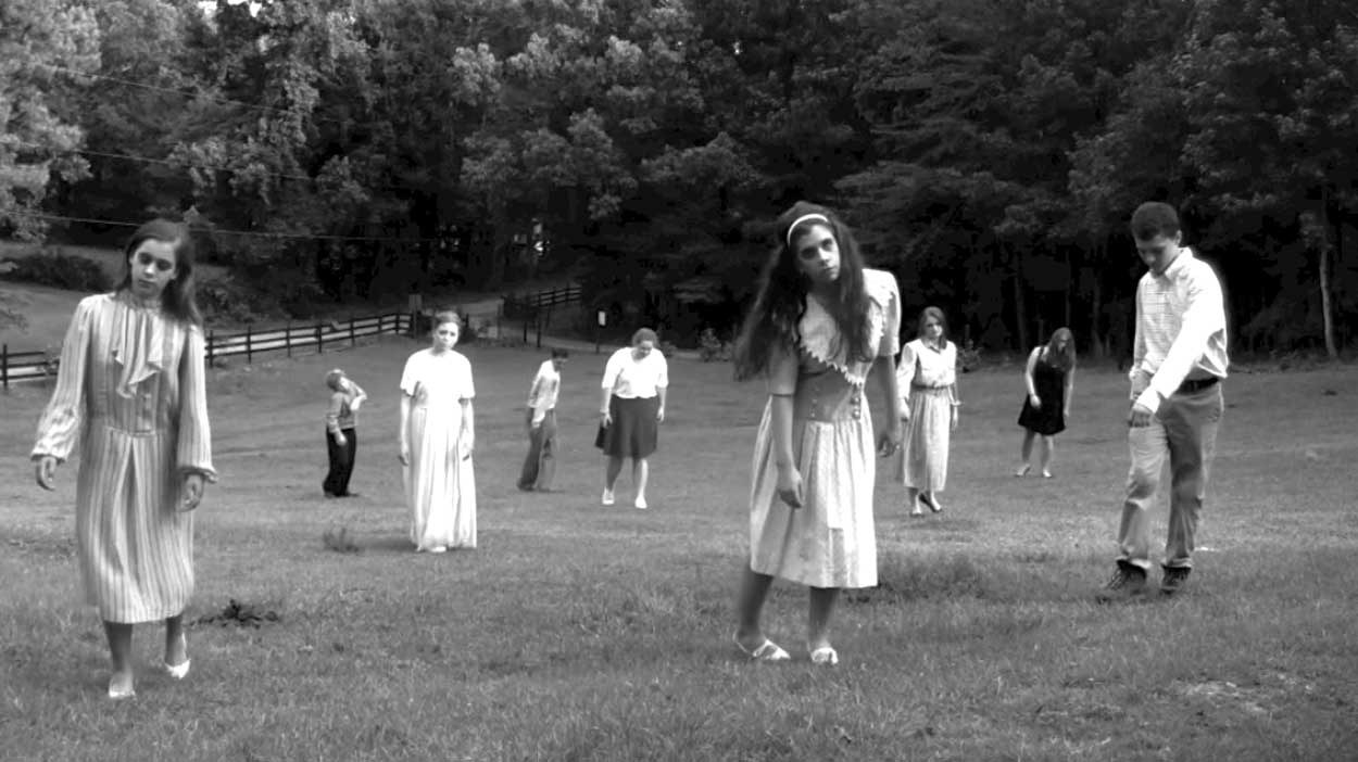 A group of dead people creepily walk through the grass