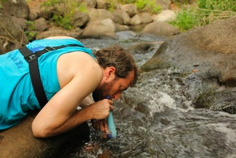 Reviewer using a LifeStraw to take a drink of water from a creek