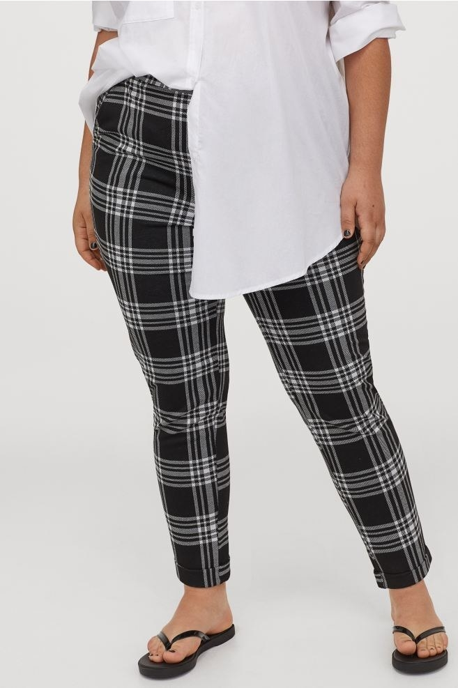 Model wearing the pants in black and white plaid