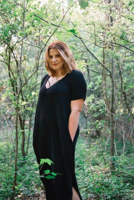reviewer wears short sleeve black maxi dress and puts hands in pockets