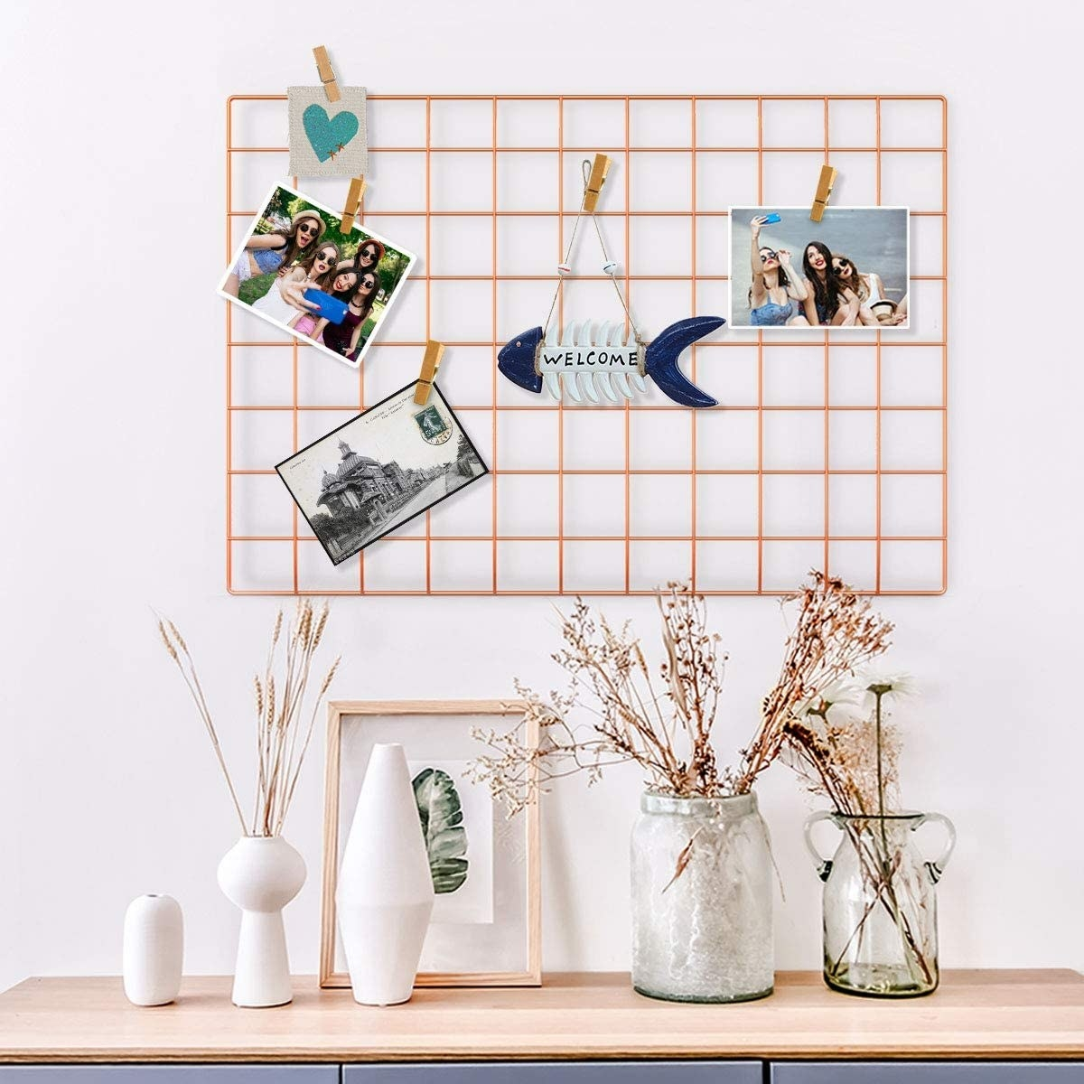 A wire wall grid is hung on a wall with pictures and mementos