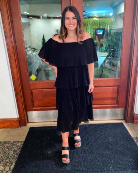 reviewer wearing a black multi-tier pleated dress with off the shoulder structure