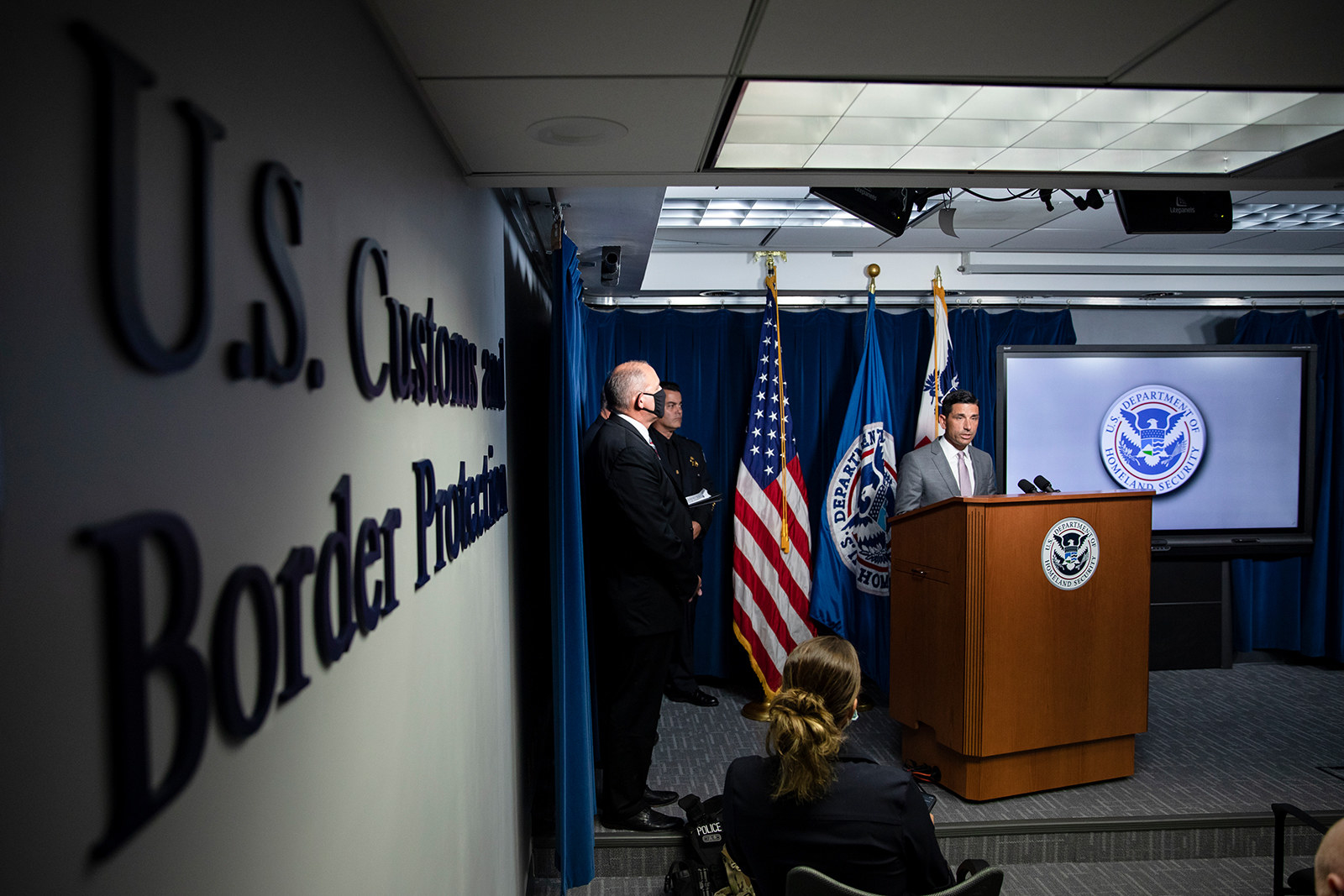 Men stand on a stage in a press briefing room