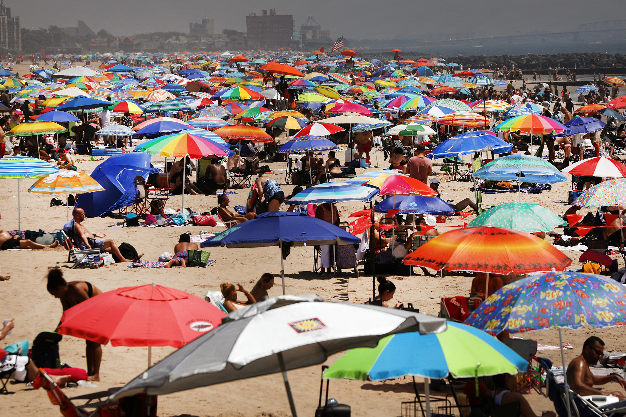 A crowded beach is filled with sunbathers and people lounging under umbrellas