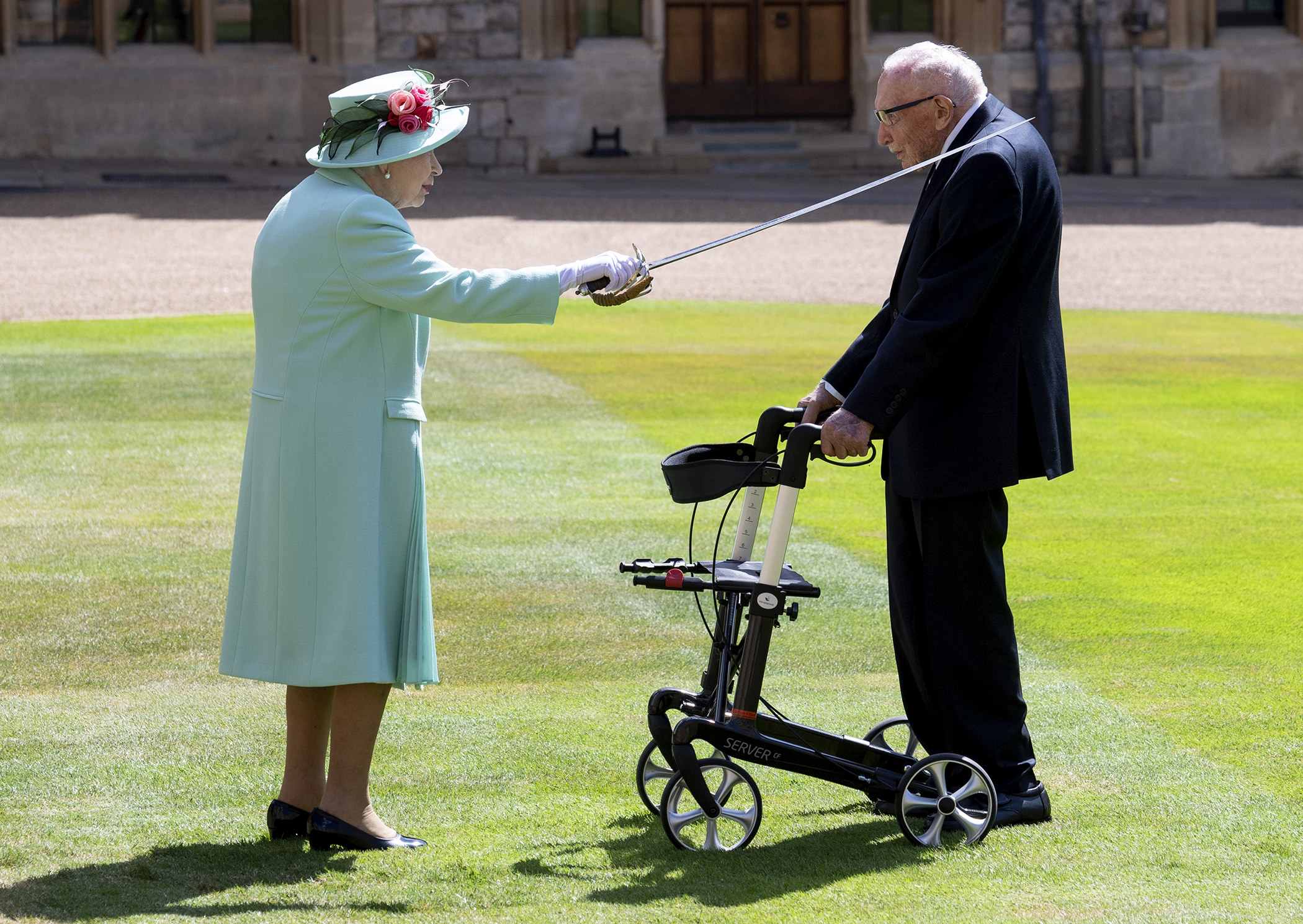 The Queen (left) uses a sword to tap the left shoulder of Sir Thomas Moore (right) as both stand on the grass