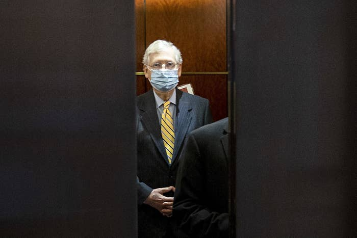 Mitch McConnell, wearing a blue mask and yellow tie, stands in an elevator as the doors close in front of him