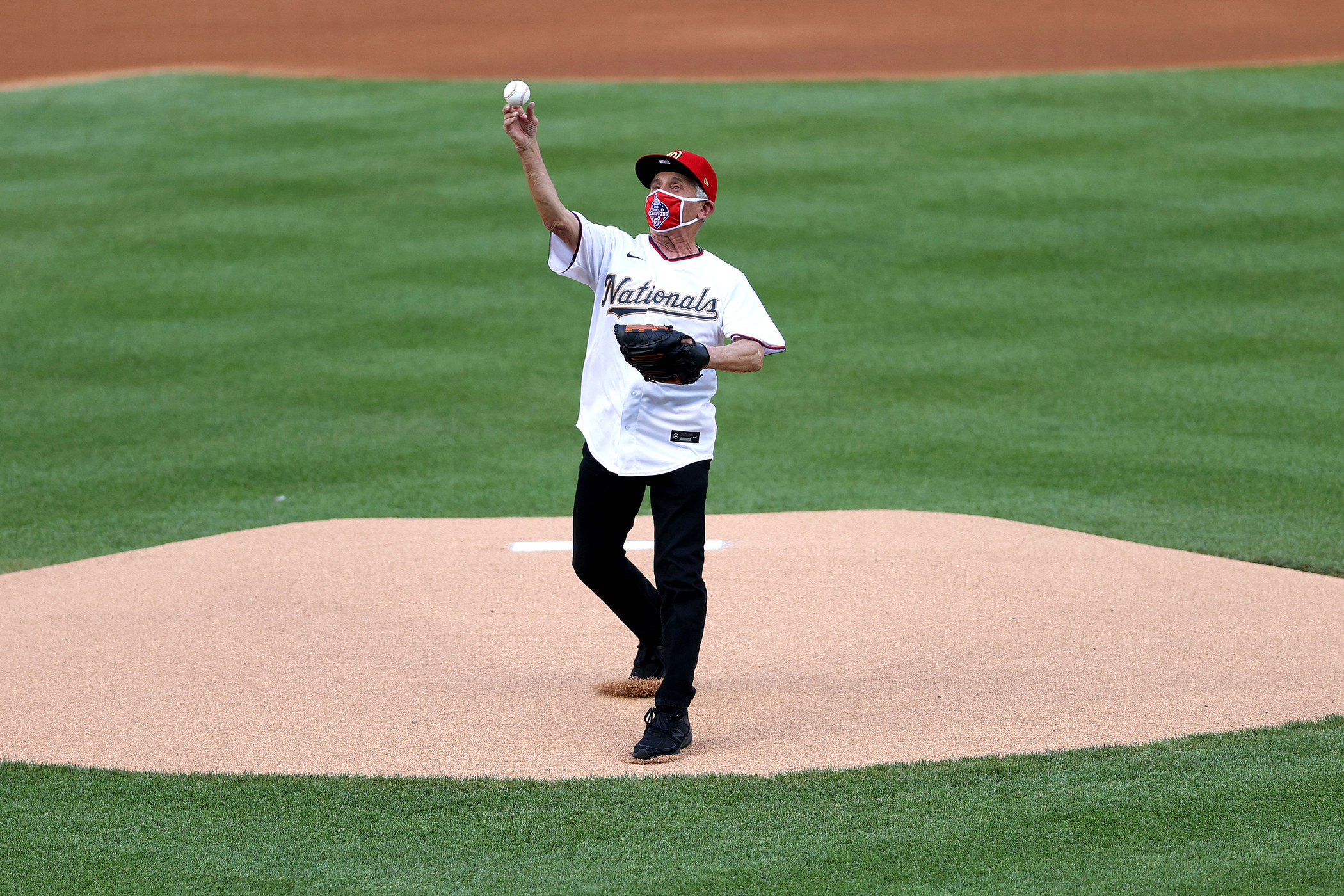 Anthony Fauci, wearing a Washington Nationals–branded cap, face mask, and jersey, stands on a mound and throws a baseball