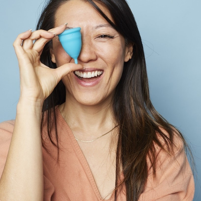 A person holds a menstrual cup up to their face