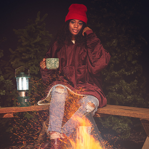 A person wears a giant hoodie while sitting out by a campfire and having a coffee