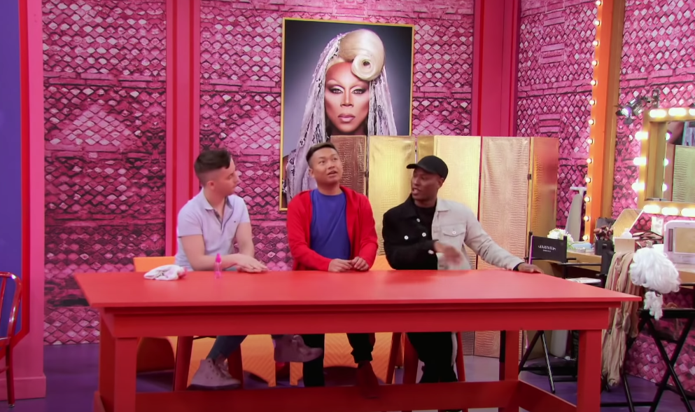 Screengrab of Miz Cracker, Jujubee, and Shea out of drag and sitting out at a red table in the Werk Room with a large photo of RuPaul behind them