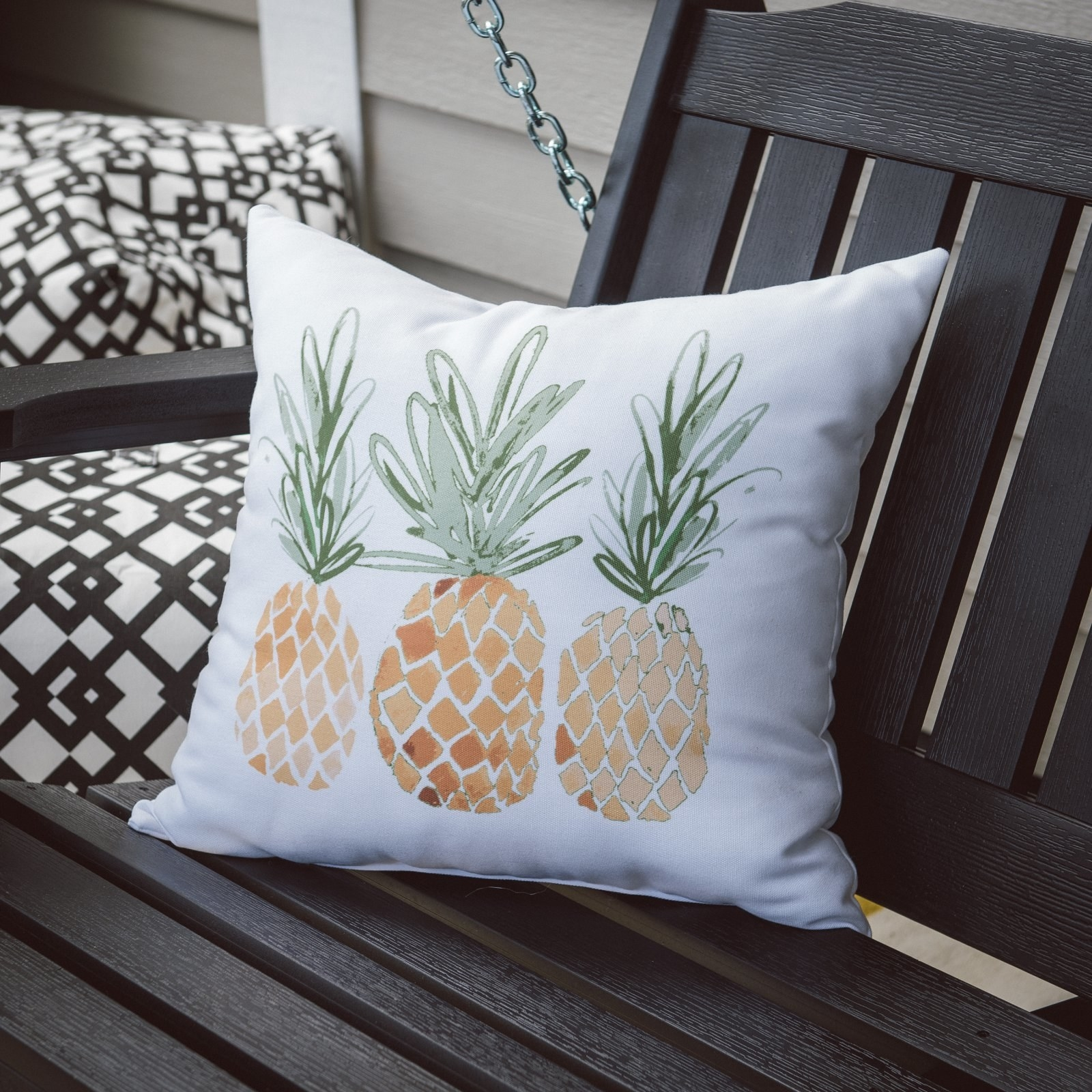 a white pillow with three pineapples on it