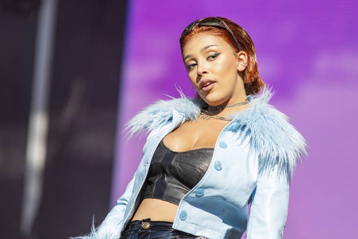 Doja Cat wears a leather bra, a jacket with a fluffy collar, and sunglasses on her head as she looks off camera while performing on stage.