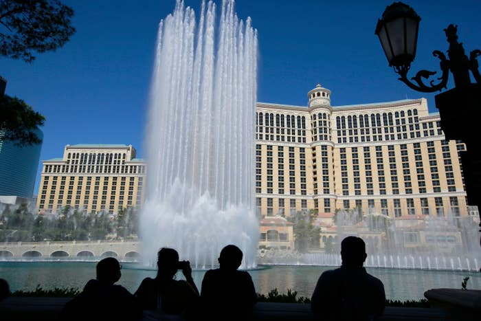Dozens of fountains shoot jets of water high into the air as onlookers watch on in front of the multi-story Bellagio hotel.