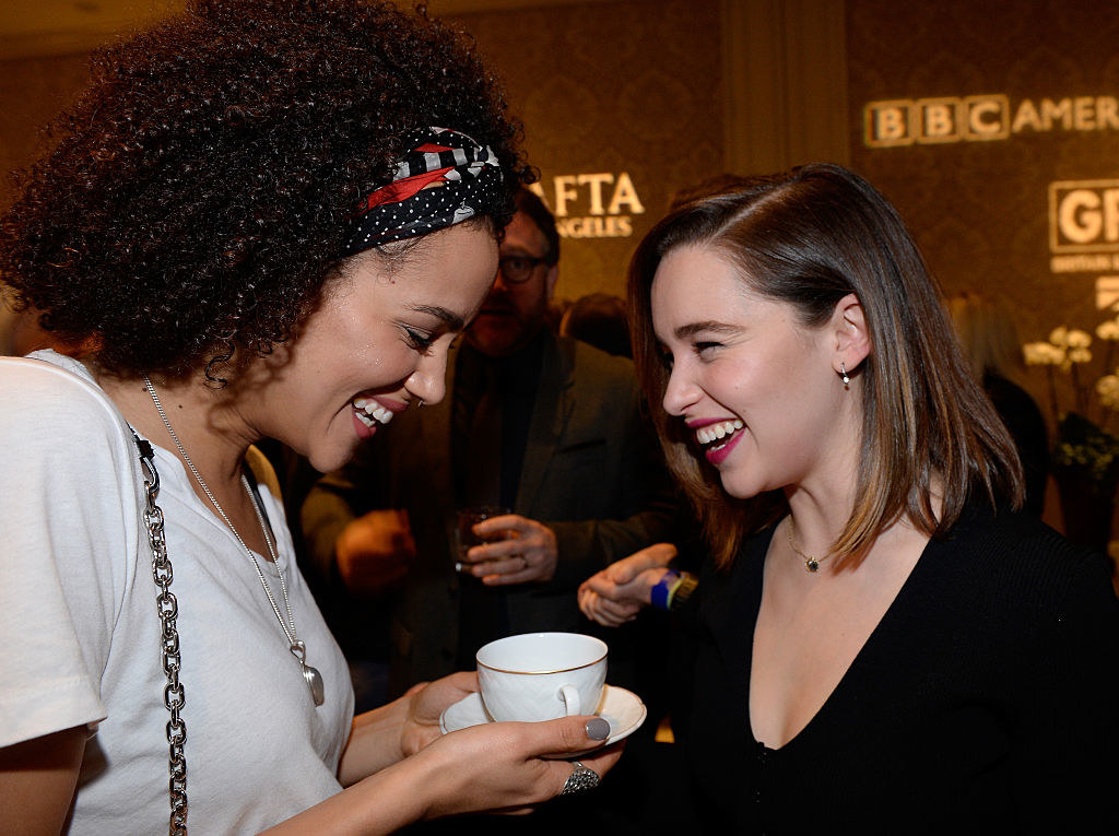 Nathalie holds a cup of tea while smiling with Emilia at an event