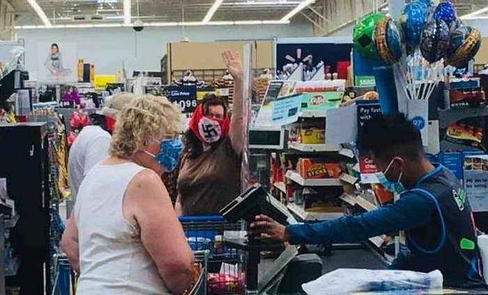 A woman wearing a swastika face covering raises her hand in the air while at a checkout.