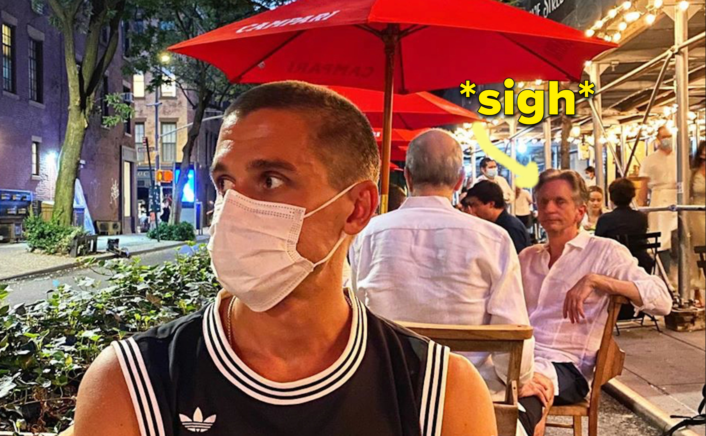 Arrow points to man staring with a straight face in the background at Antoni