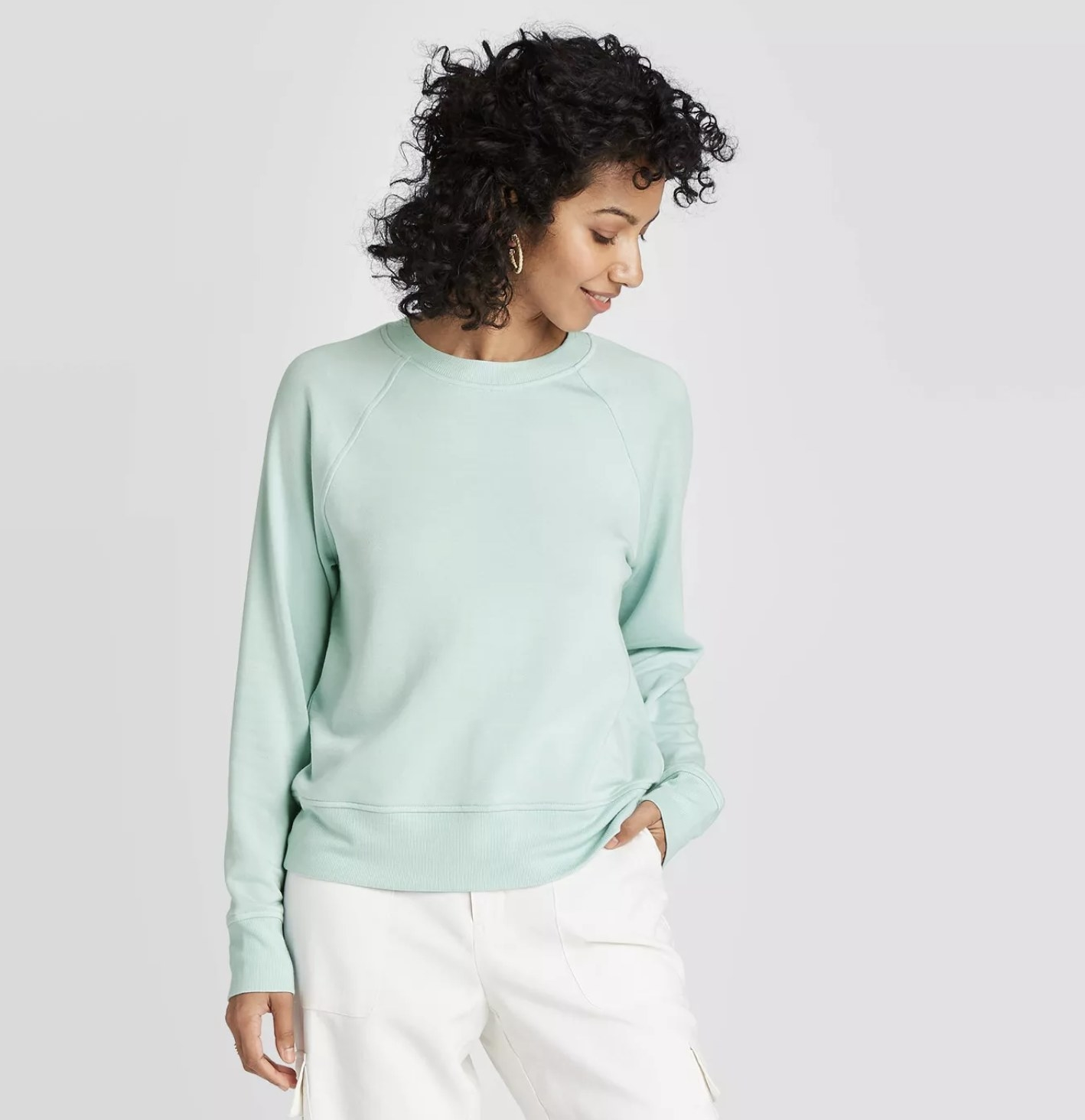 A model wearing the mint green sweatshirt