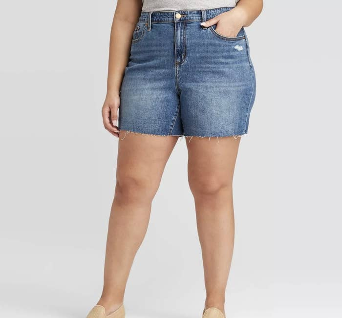 A model wearing a pair of jean shorts that hit mid-thigh