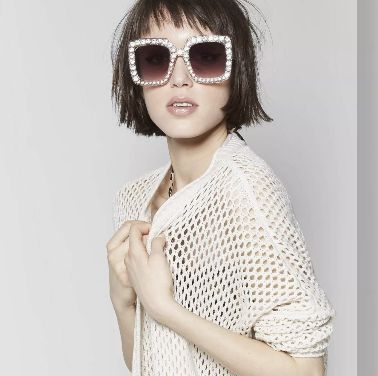 Model wearing square glasses with rhinestone accents