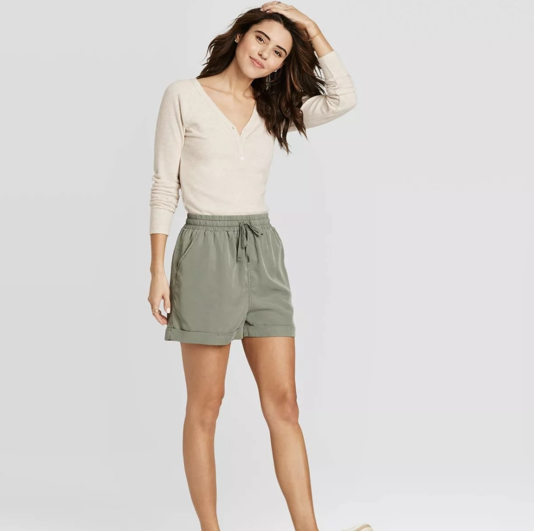 Model wearing olive green shorts that hit mid thigh
