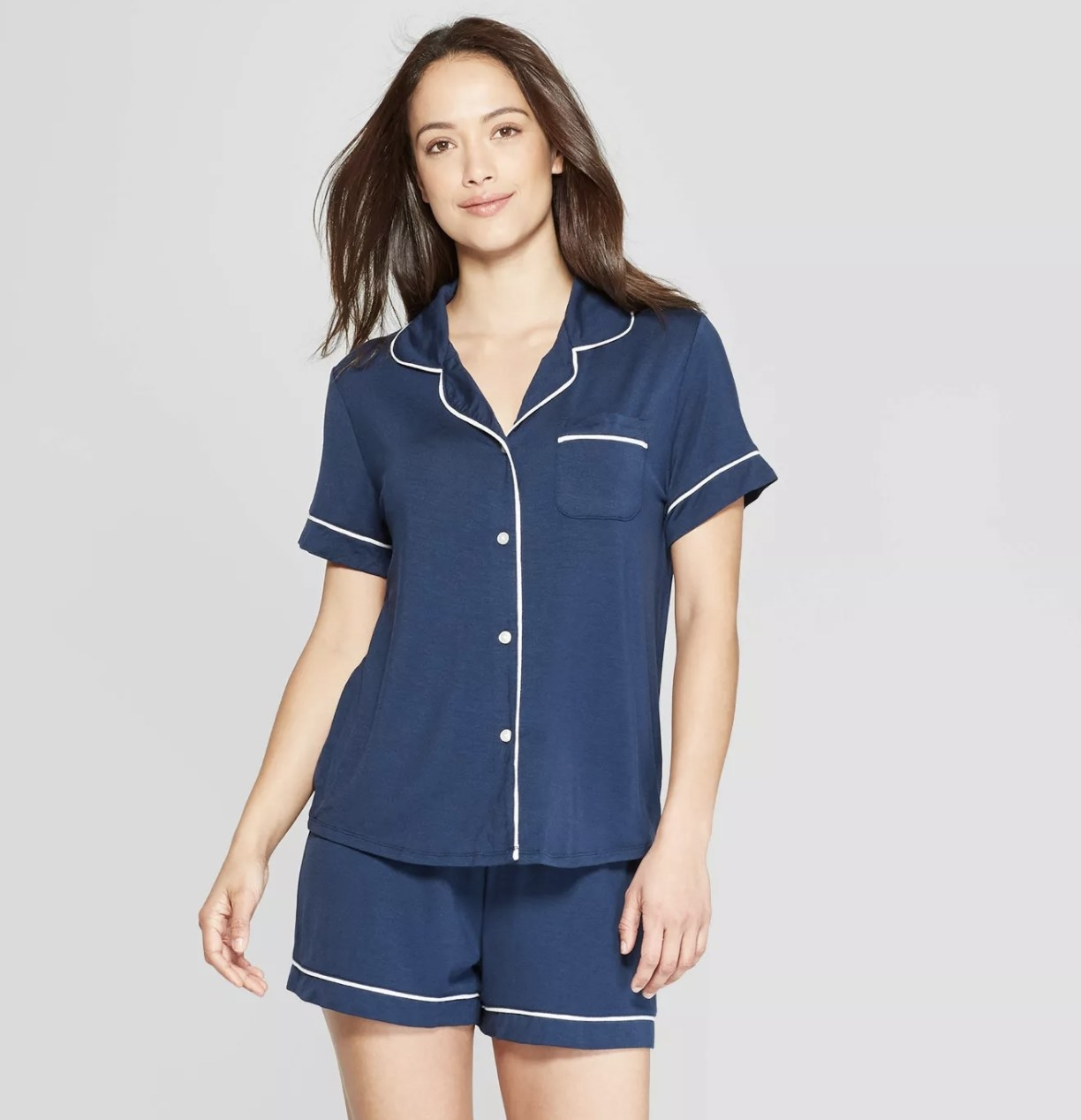 A model wearing a set of short sleeve and short shot pajamas in blue with white piping