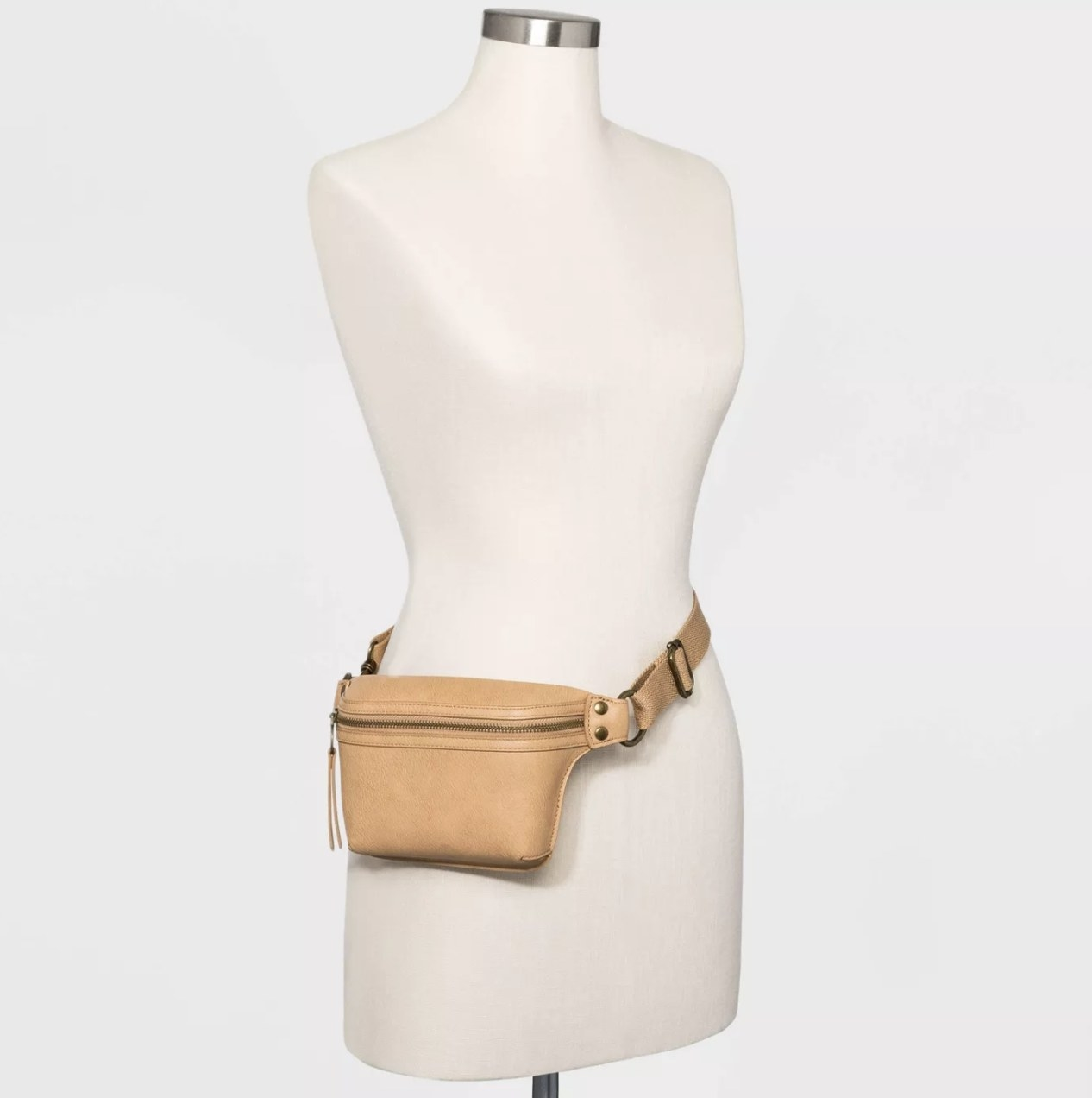 A faux-leather light tan fanny pack worn on a mannequin
