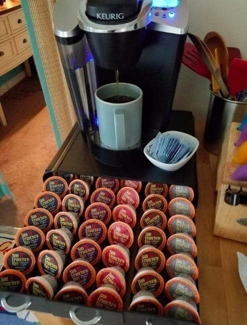 The drawer underneath a Keurig, opened and holding various coffee pods