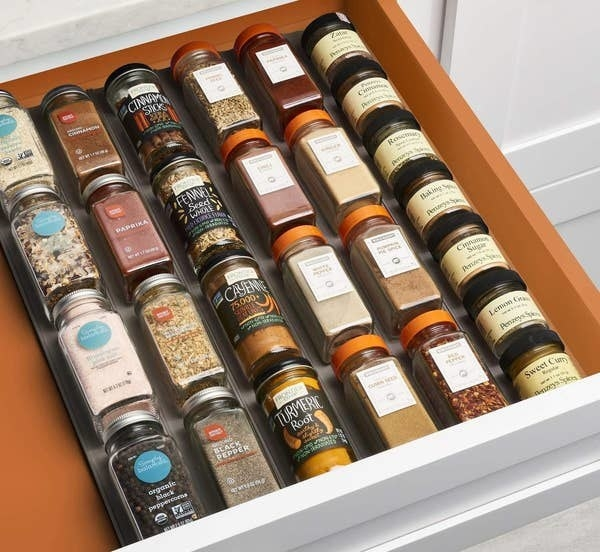 a grey mat covered in spice jars in a drawer