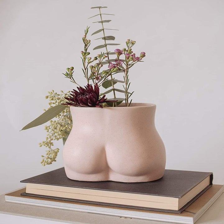 the pink speckled vase in the shape of a butt holding flowers