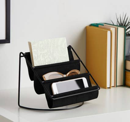 The hammock organizer on a desk filled with a phone sunglasses and a notebook