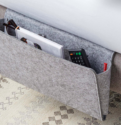 The storage caddy packed with a remote control glasses and a notebook and tucked under a mattress