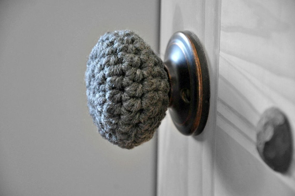 A round doorknob with a gray knitted cover