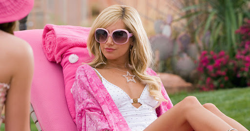 Sharpay sitting on a lawn chair outside wearing a bathing suit and sunglasses, with a confident expression on her face, basking in all of her beautiful glory