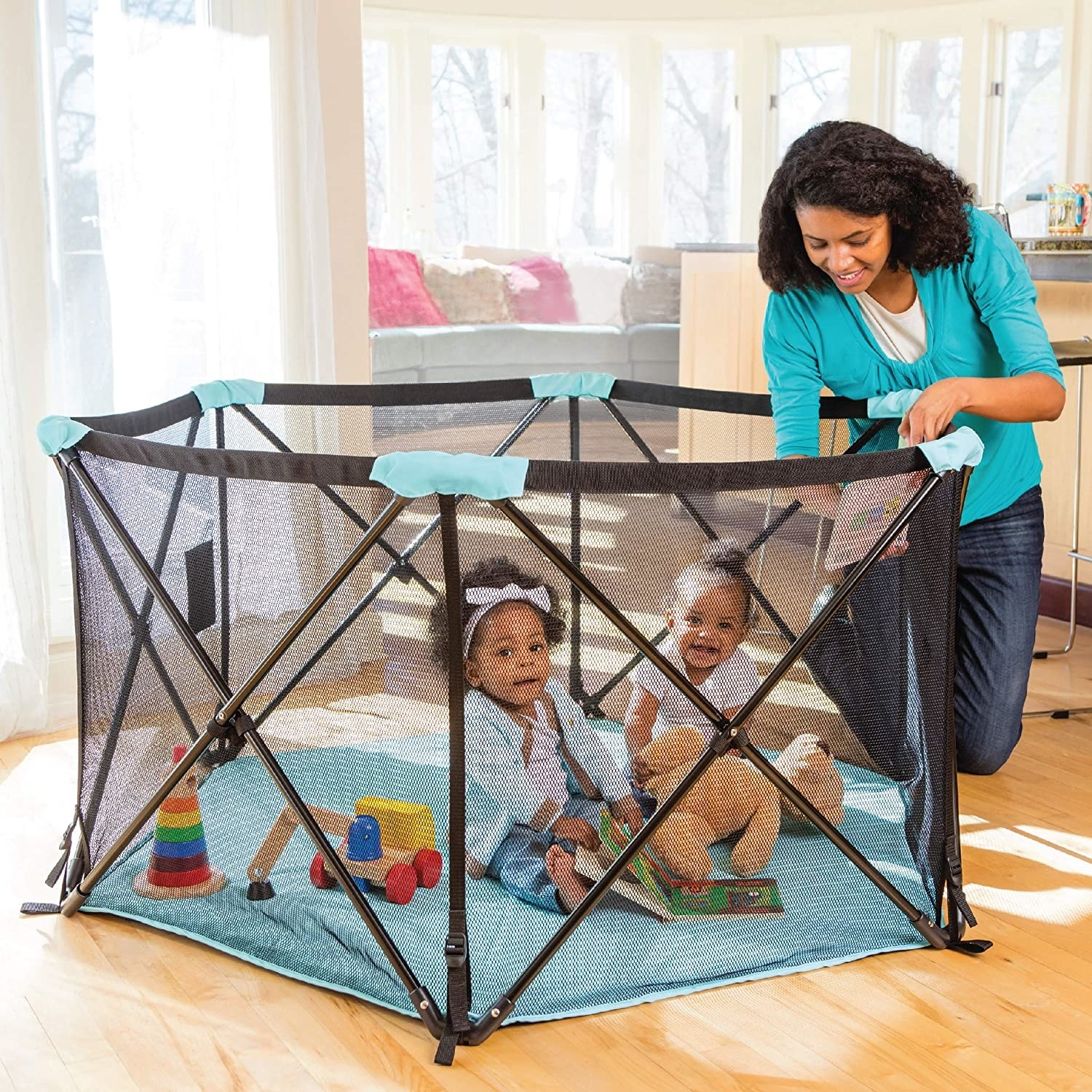 Two young children inside the play space while indoors. There is plenty of room for them both to move around, even with several toys inside.