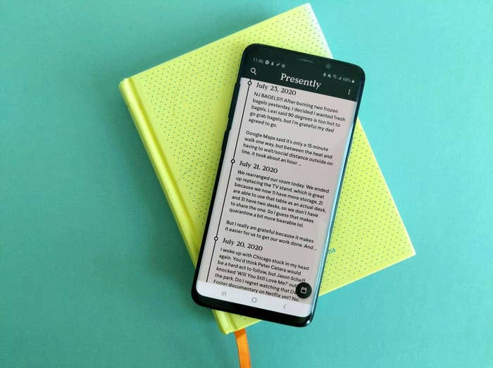 A phone showing the Presently app opened, it sits on top of the Two Minute Morning journal
