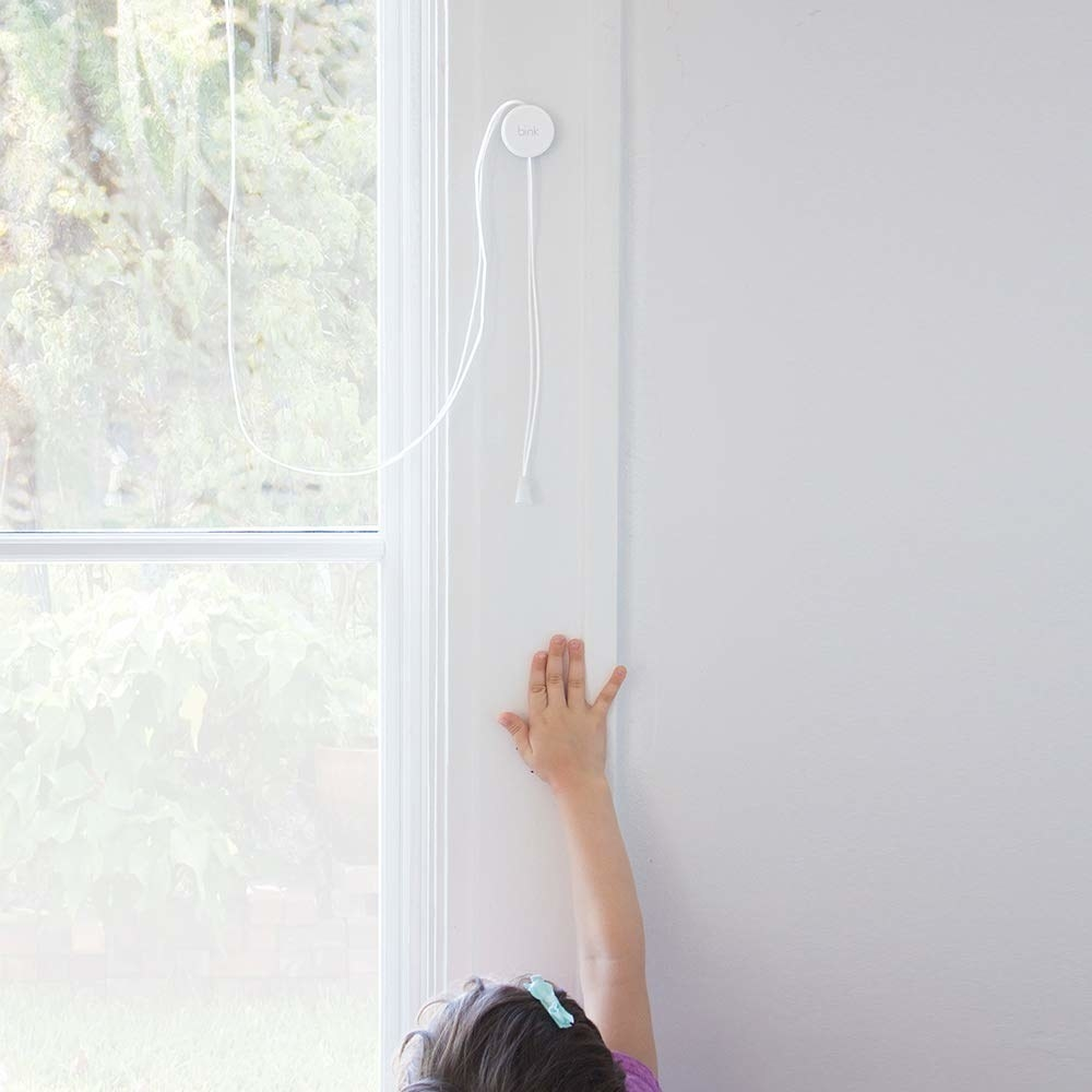 A child stretching up to reach the blind cord by the window without being able to reach it because the cord is wrapped around the round holder
