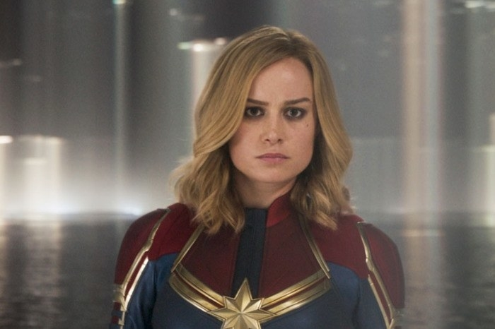 Captain Marvel staring at someone with a serious expression on her face, wearing her superhero suit, hair down to her shoulders