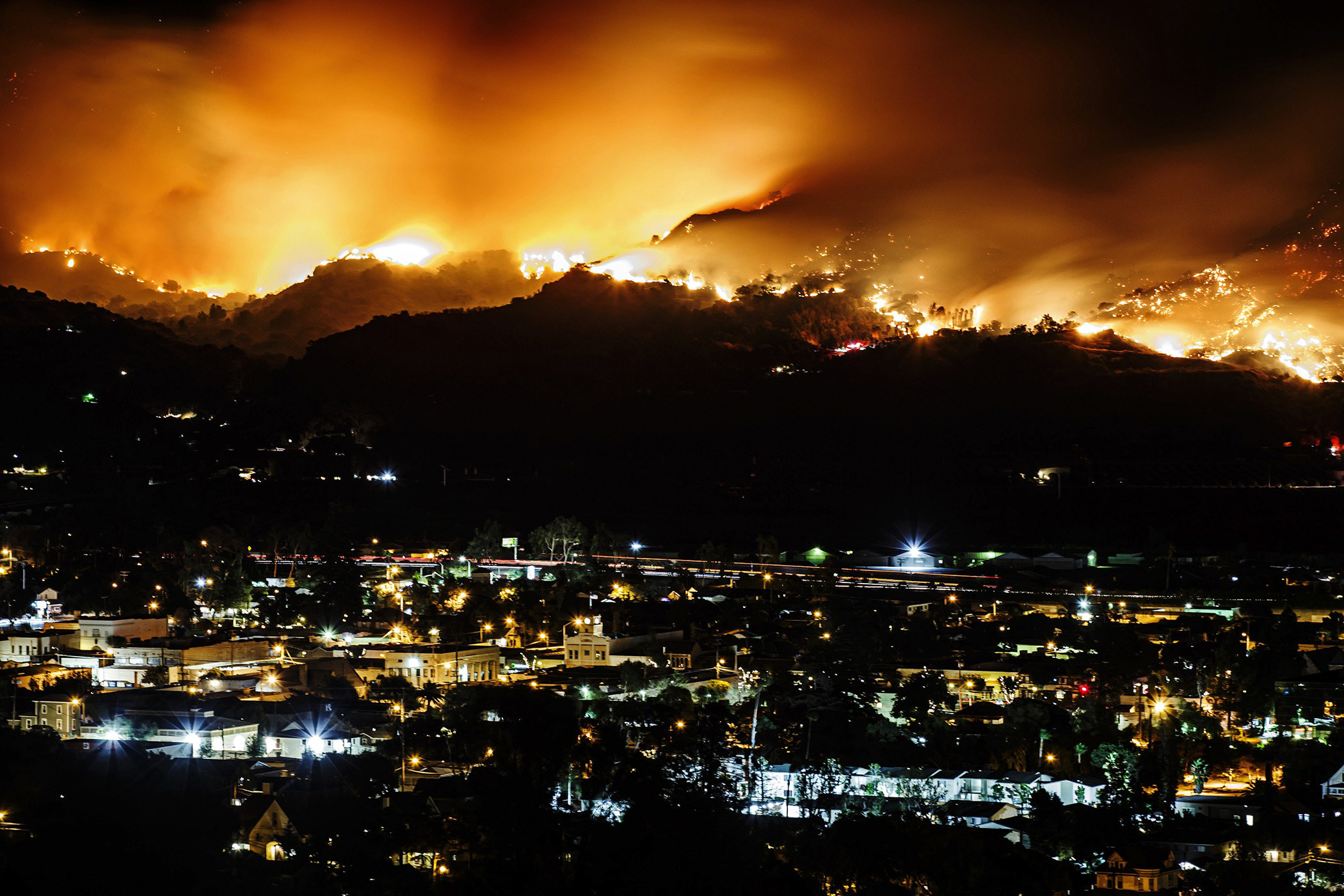 A city skyline at night is illuminated by wildfire flames