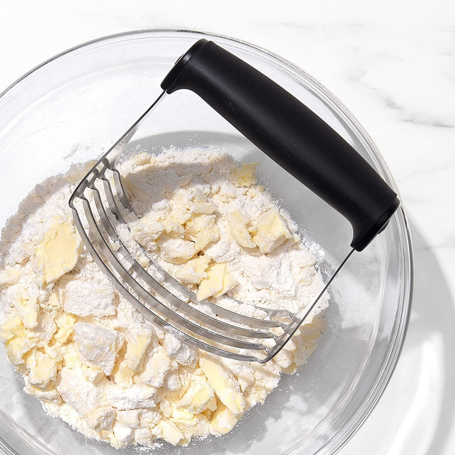 The pastry blender with a handle and five blades immersed in a bowl of flour