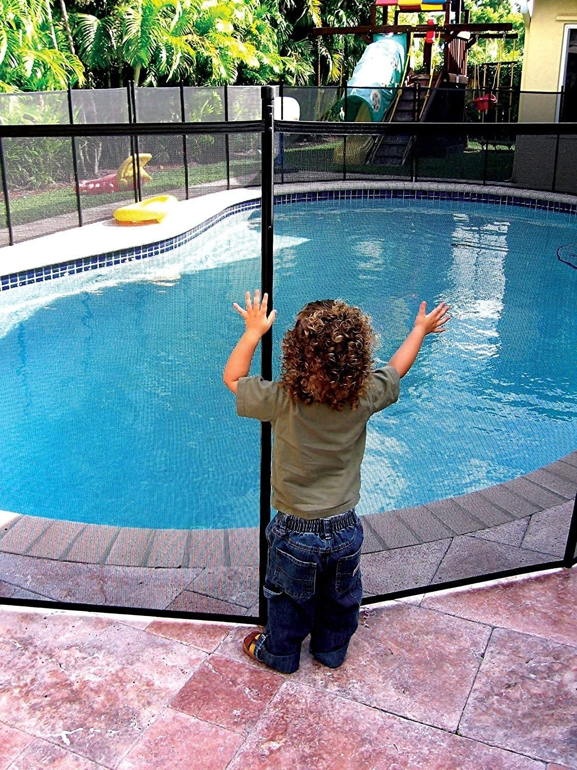 A child pushing against the mesh pool gate without being able to get through