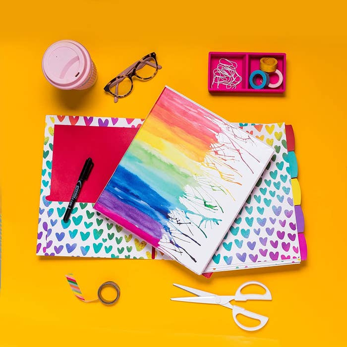 A binder with a rainbow water colour painting on the front There a set of a page dividers and a notebook underneath and a pen, scissors, tape, glasses, and coffee cup nearby