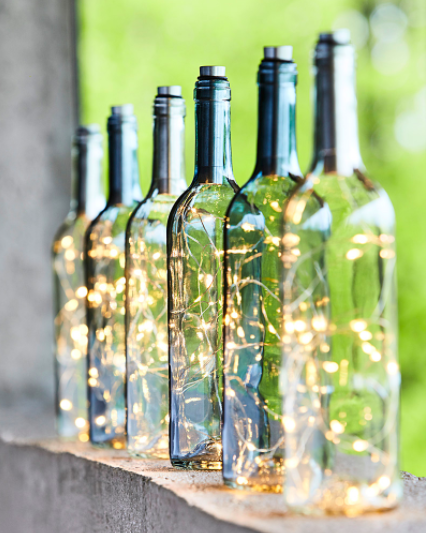 A neatly arranged row of bottle lights perched on a ledge