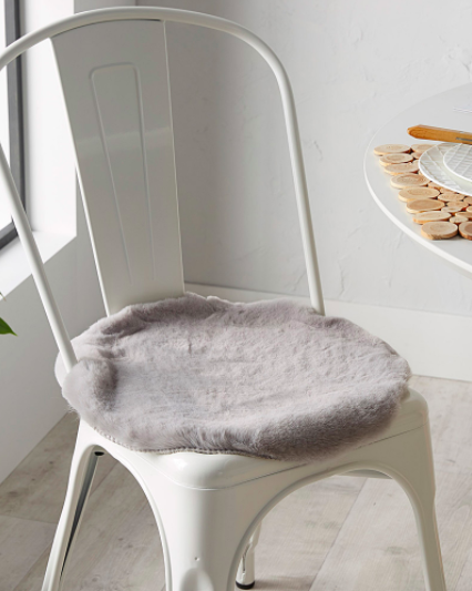 The faux sheepskin pad tossed onto a metal chair