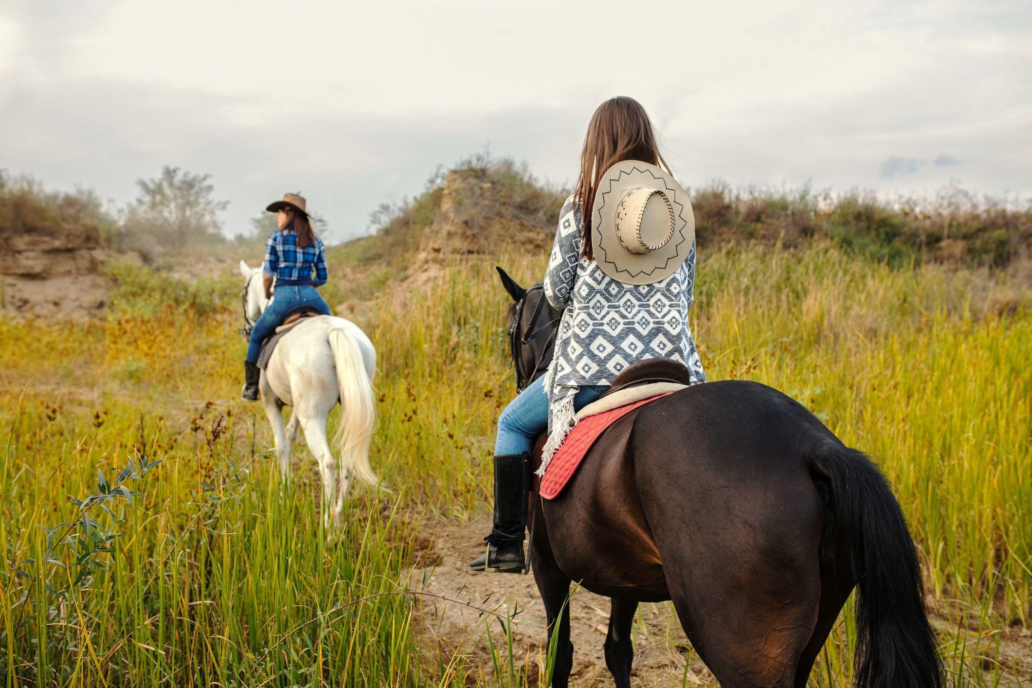 Two women on a trail ride with horses.